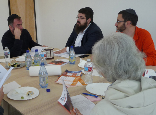 A Torah class meets during lunch hour at the Center for Jewish Life, opened in March for East Side services and activities. Class members include Fred Stiber, left, Rabbi Chaim Wilhelm, Oleg Sotnik and Tehila Vanfossen. (Janet Goetze)