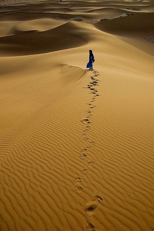 This image has an empty alt attribute; its file name is woman-walks-desert-sands_ii.jpg