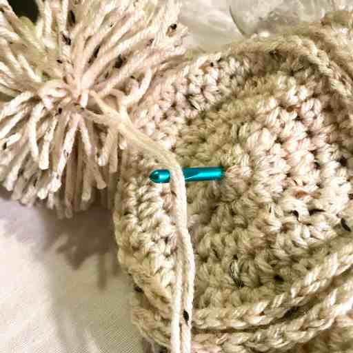 DIY attach pom pom to had using a crochet needle or a sewing needle