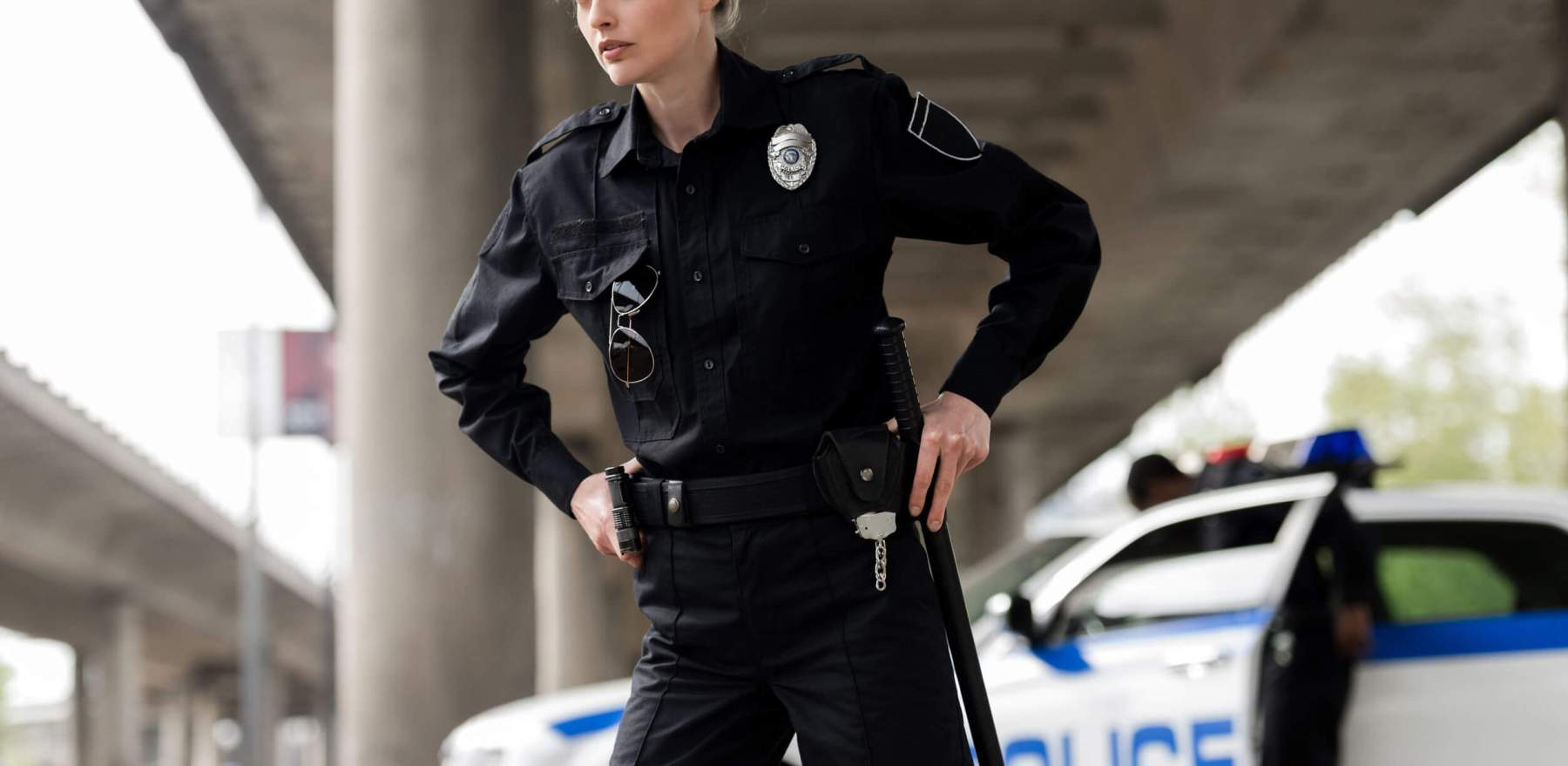 confident female police officer looking away and taking out gun and bat