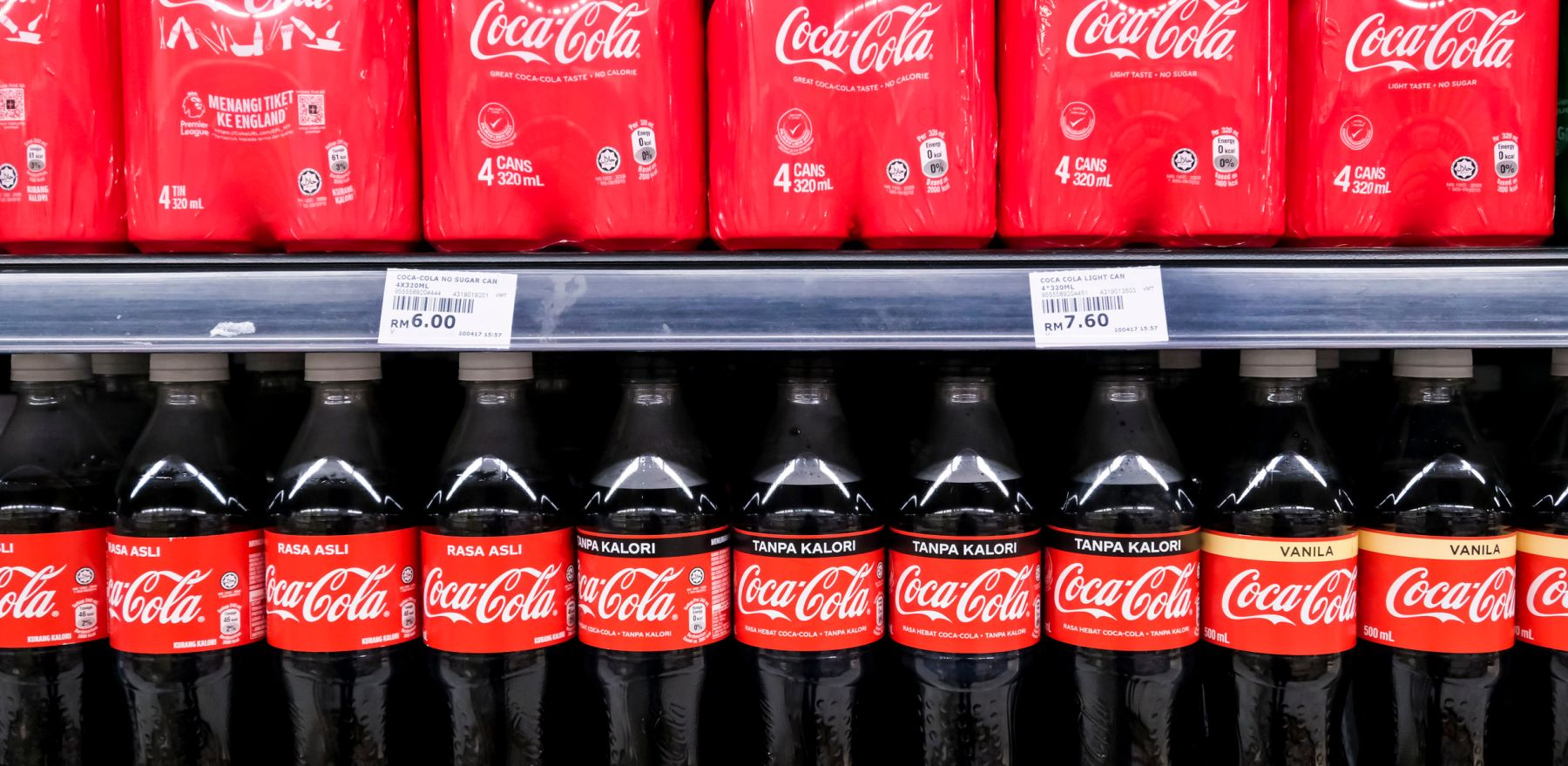 KUALA LUMPUR, MALAYSIA - MAY 04, 2020: Coca Cola product in bottles and cans on the shelves in a grocery store supermarket. Coke is a carbonated soft drink produced by The Coca-Cola Company.