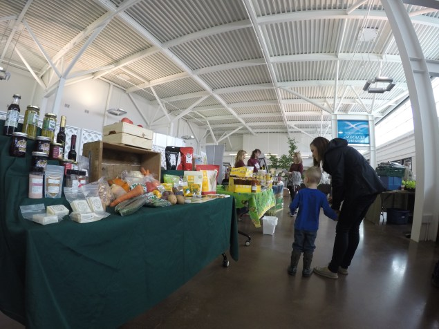 EcoLiving Fair attendees check out vendors including locally produced honey