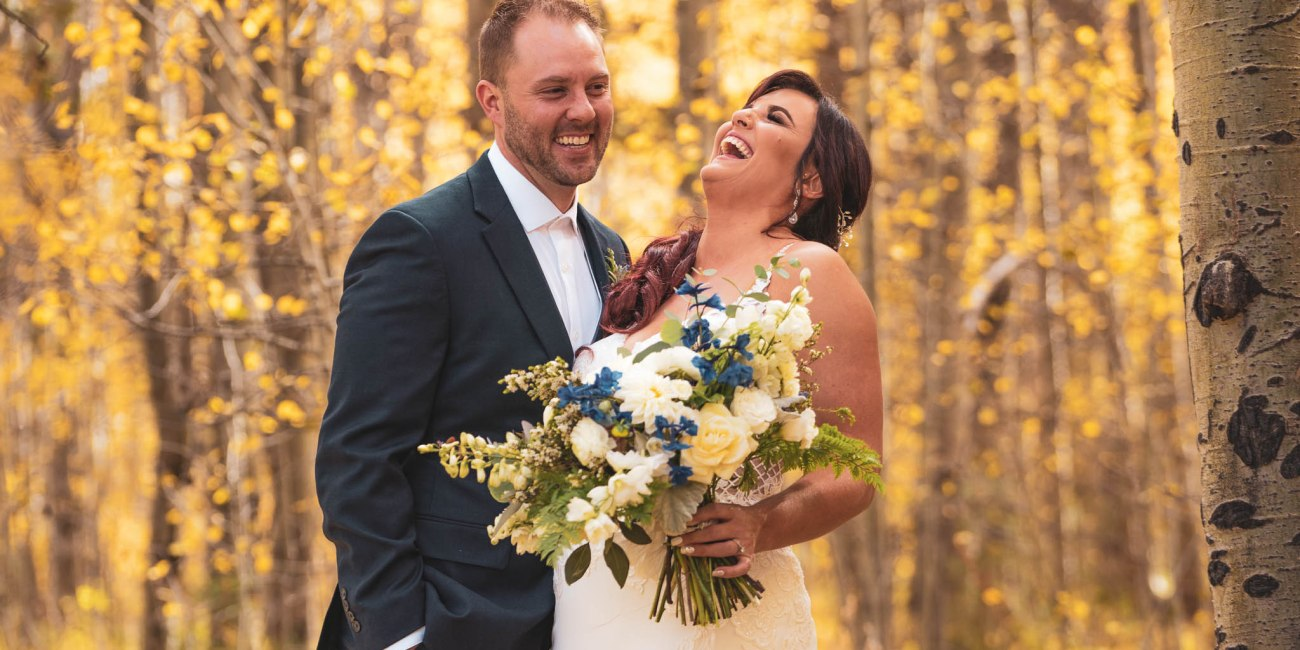 Bride laughing and groom smiles with yellow aspens around them
