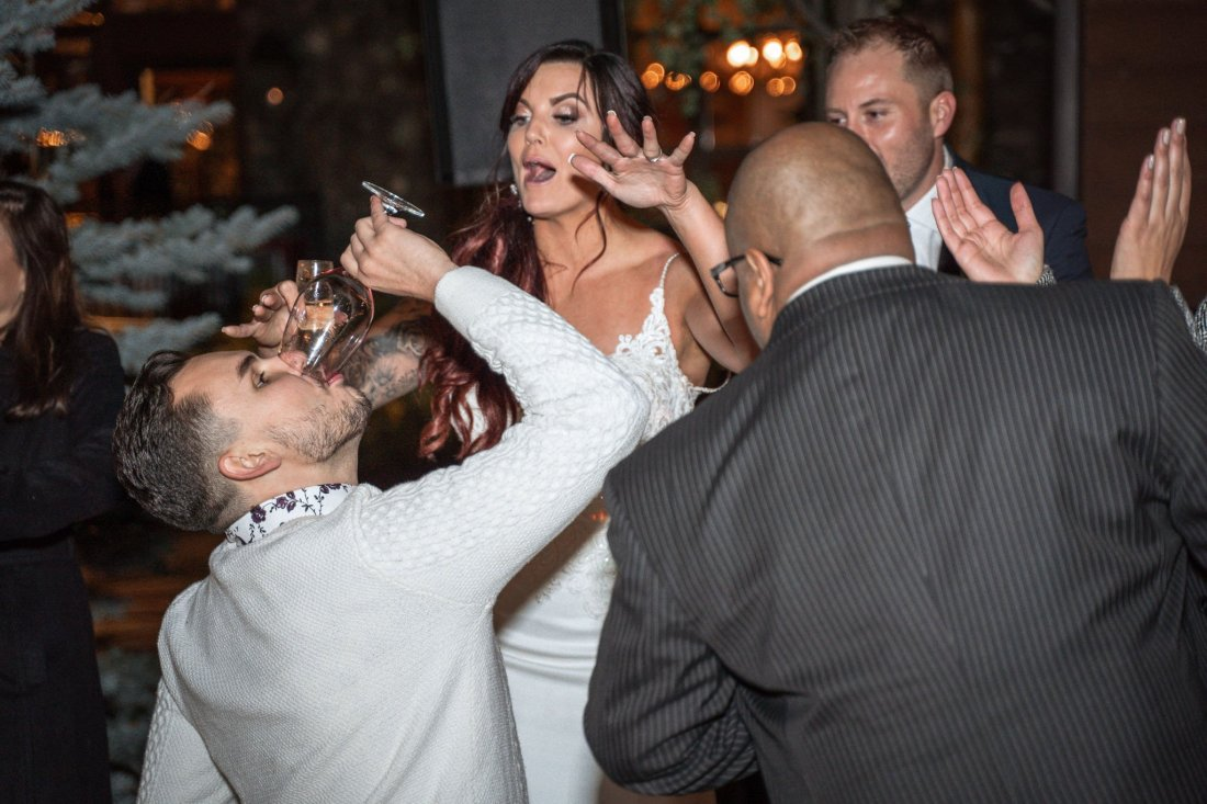 Dance party with man and bride drinking wine while dancing