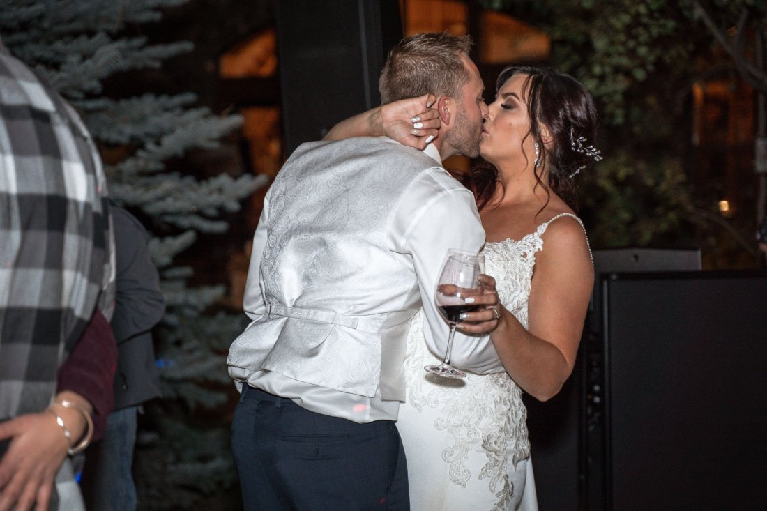 Groom kisses bride as they dance at the wedding reception