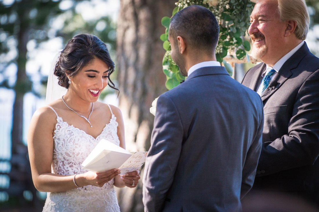 Bride says her vows to the groom, with the minister looking at them