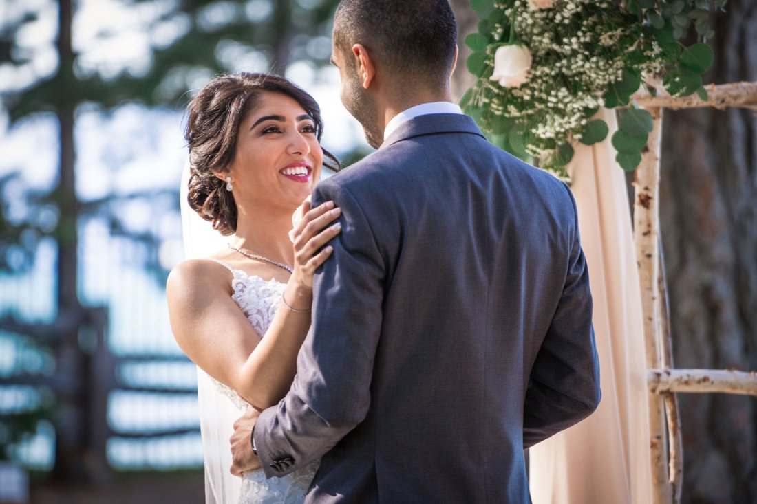 Bride looks longingly at the groom as they finish exchanging rings