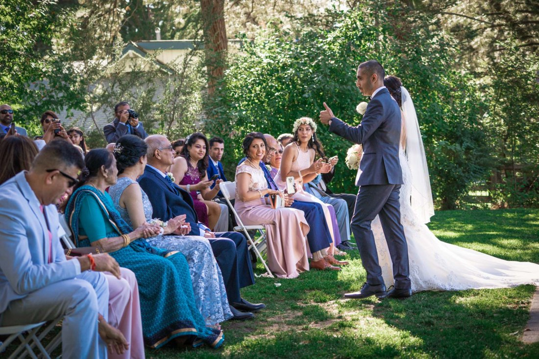 Guests clap and cheer as the couple walks down the aisle, officially married