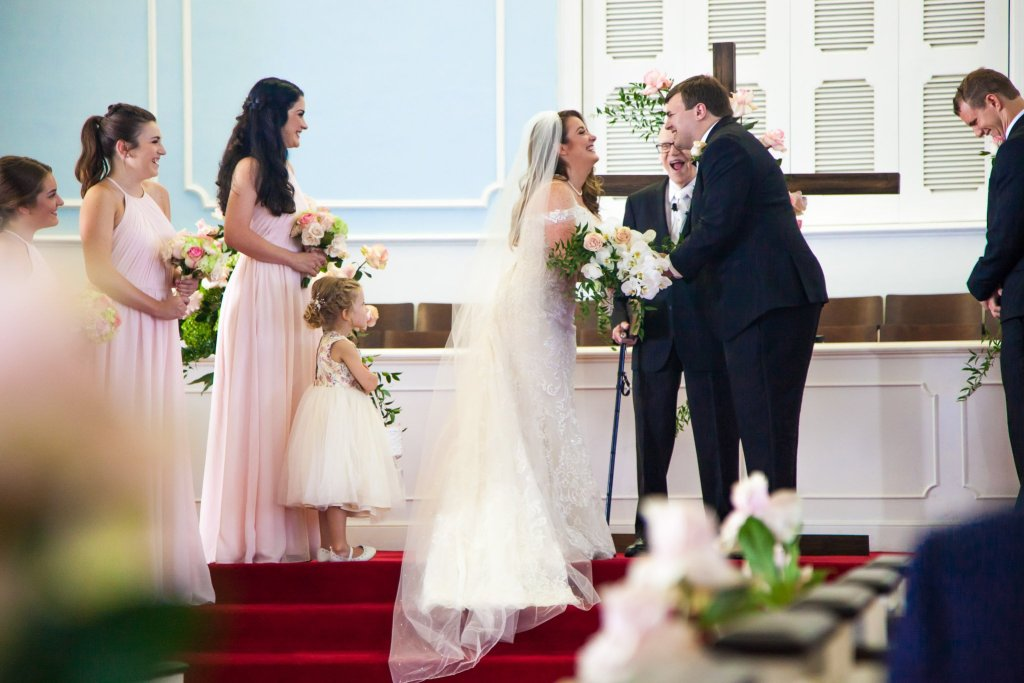 Church wedding ceremony with the bride and groom laughing and smiling during wedding photography