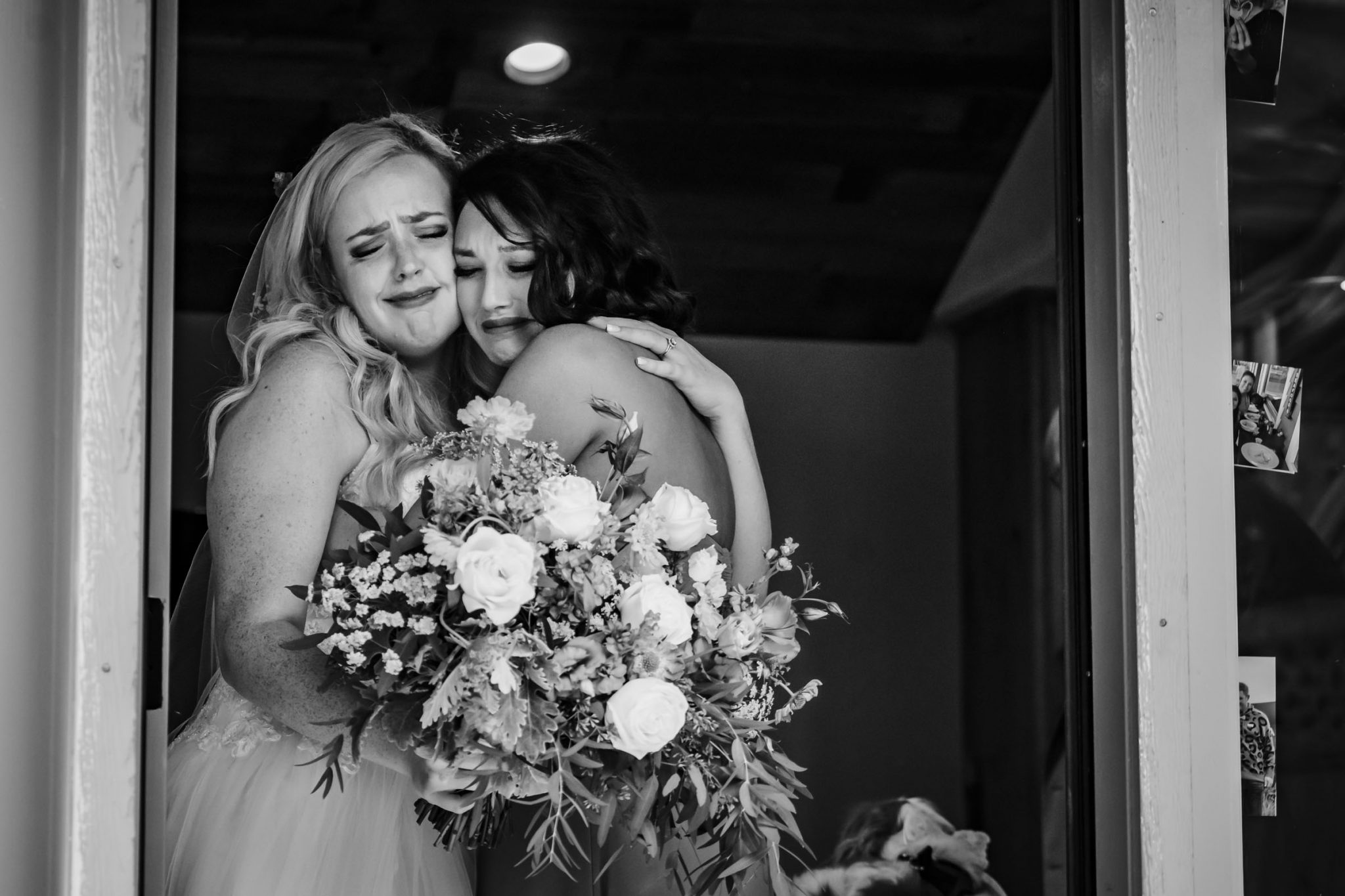 Bride and her maid of honor are hugging and crying