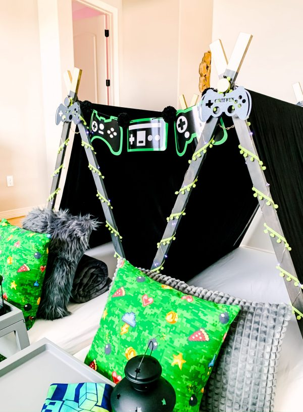 Slumber party tents with black covers and video game decor.