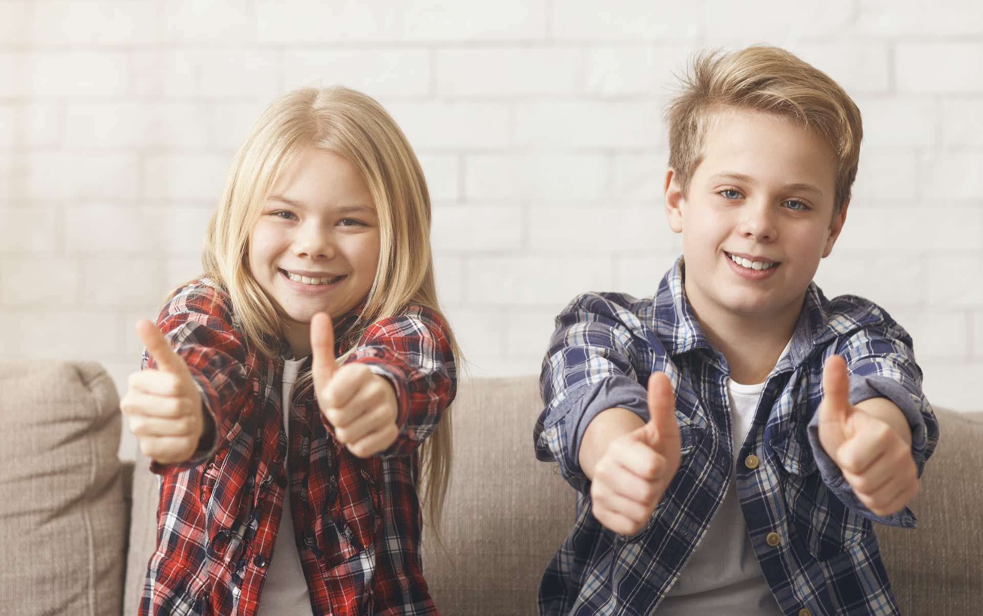 Cheerful Brother And Sister Siblings Gesturing Thumbs Up Smiling To Camera Sitting On Couch At Home. Selective Focus