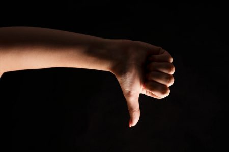 White female hand making thumb up gesture at black isolated background. Closeup of positive sign, like, agreement concept, copy space