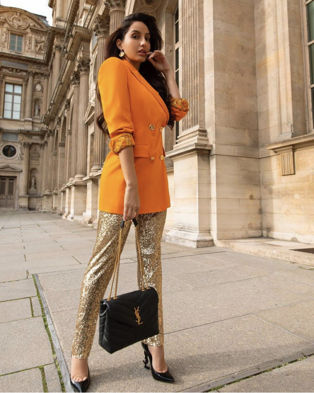 Nora Fatehi pairs orange Versace blazer worth 1.2 lakhs with shimmery pants and YSL bag worth Rs. 1.5 lakhs