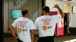 Carlos Aponte, left, executive director of We Love Philly, and Jason Peters, Philadelphia area podcaster, show off t-shirts before beginning their 62-mile fund-raising walk from Philadelphia to Atlantic City on Saturday, July 17, 2021.