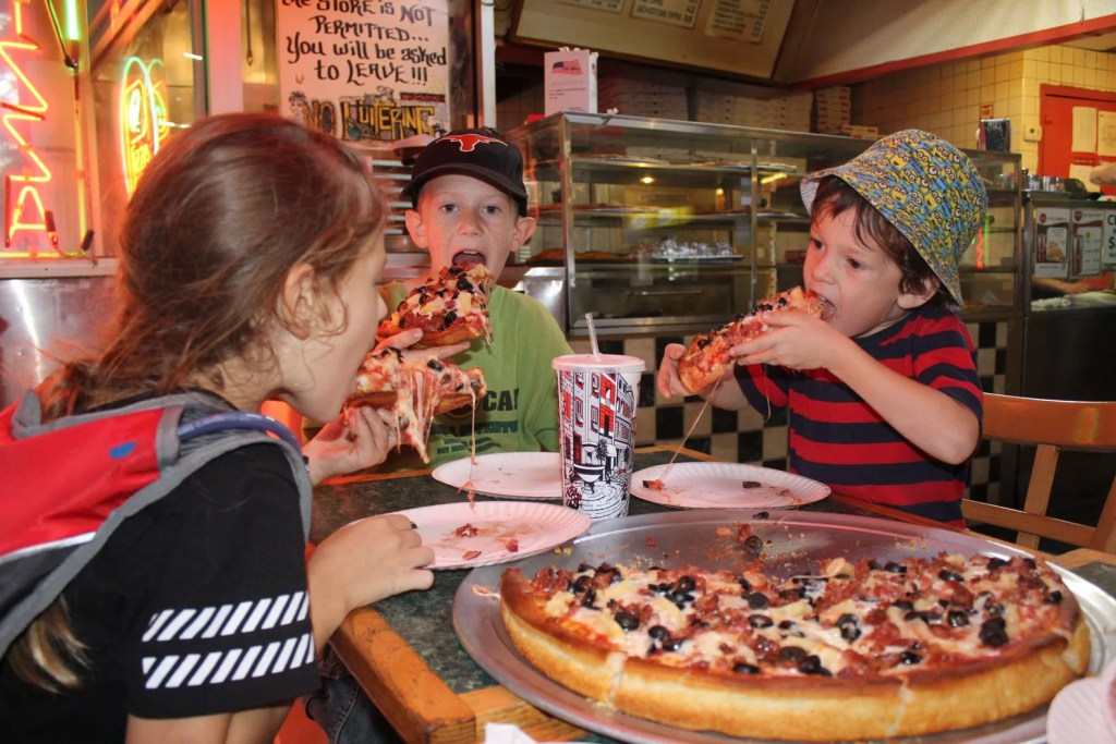 Three kids eating pizza in a restaurant.