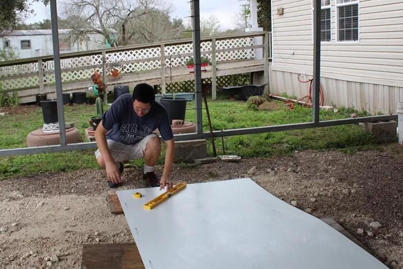 Man putting fiberglass sheet on ground