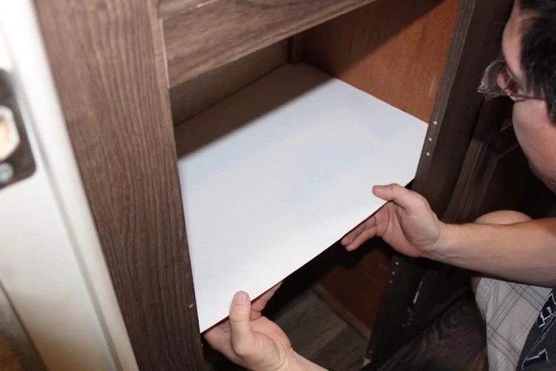 Two hands holding shelf where it will go
