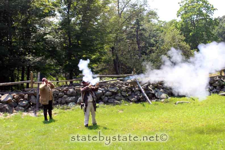 Two historic actors firing a musket