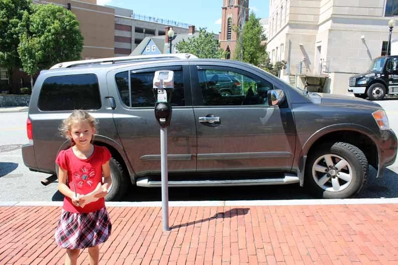 A little girl standing in front of a car parked by a parking meter.