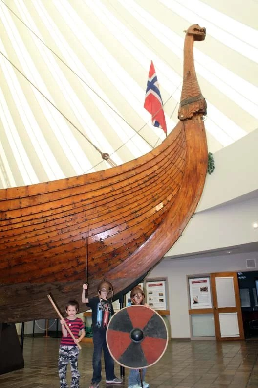 Three kids with viking weapons in front of a viking ship!
