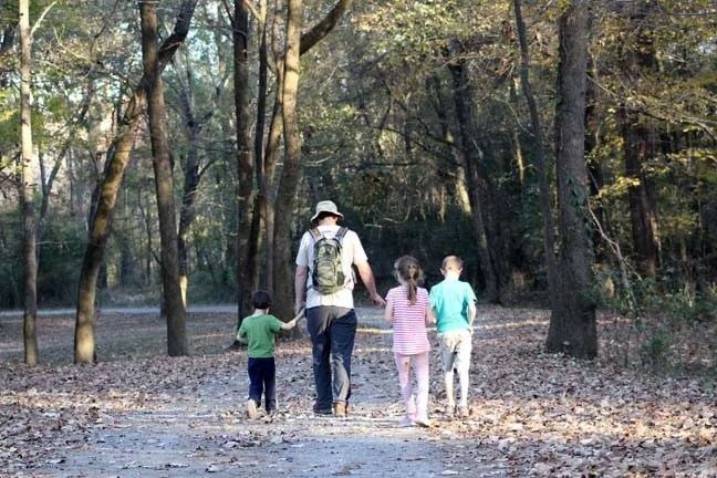 A family hiking in the woods together.