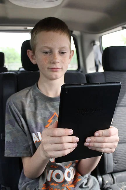 A boy reading on his tablet while traveling.