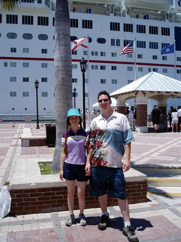 A husband and wife in front of a cruise ship.
