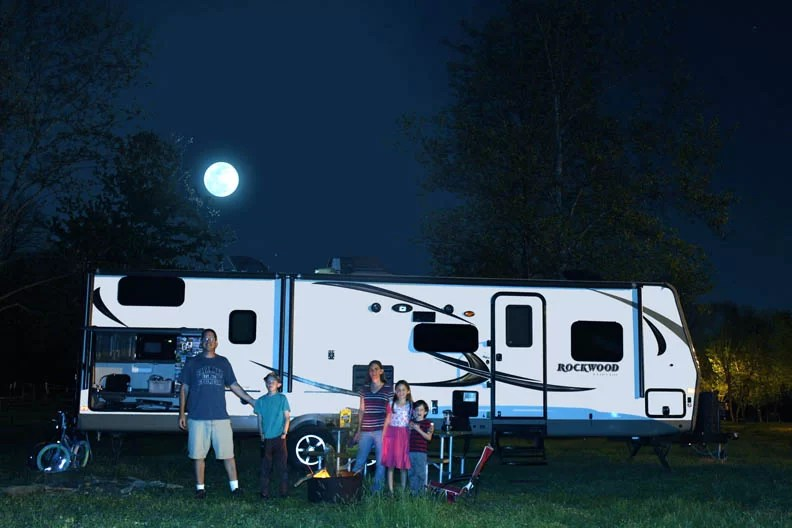 A family in front of their RV.
