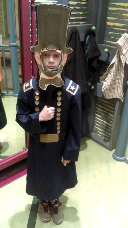 A little boy dressed as a soldier.