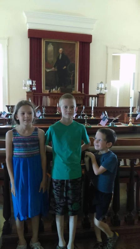 Three kids in the chambers with a picture of Washington behind them.