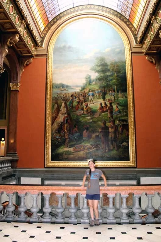 A woman in front of a large oil painting.