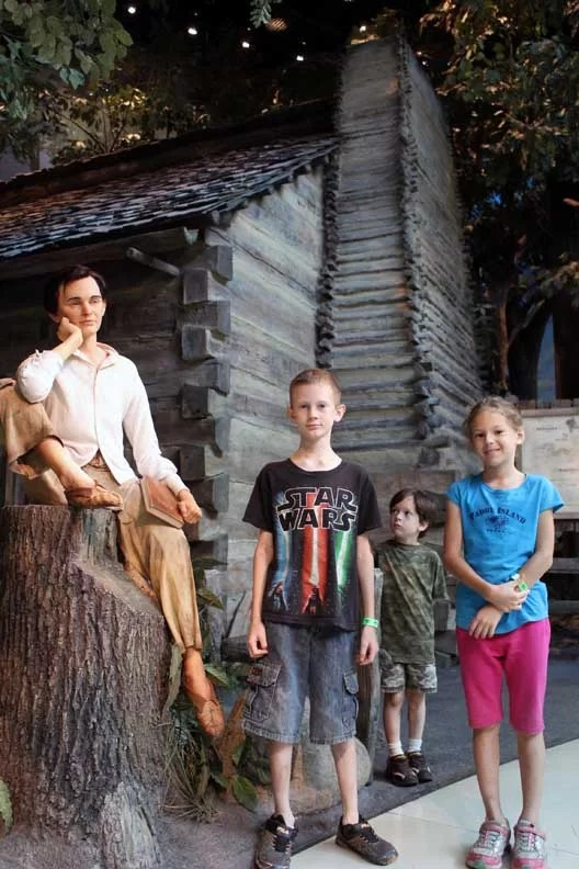 Three kids next to a wax sculpture of Lincoln.