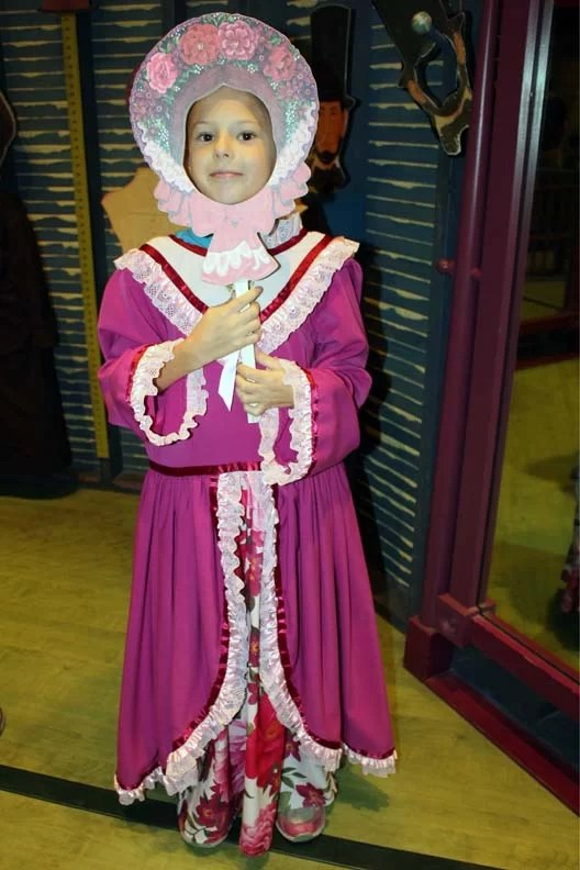 A little girl dressed up in old period clothes.