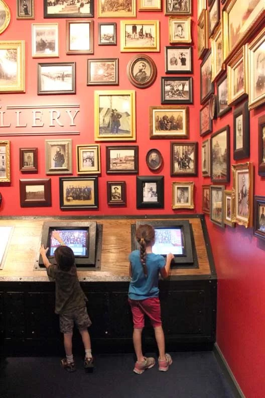 Two kids using computers to learn about historic pictures.