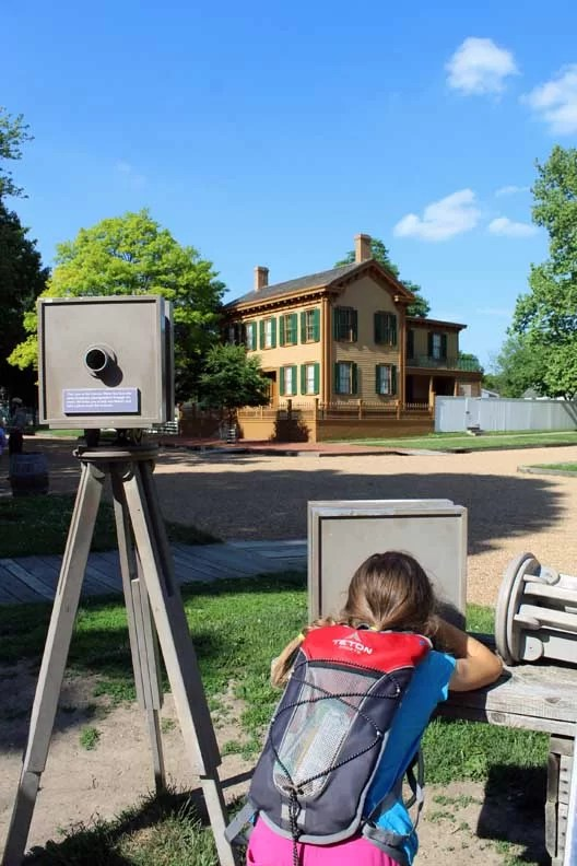 A little girl looking through an old camera at Lincoln's house.
