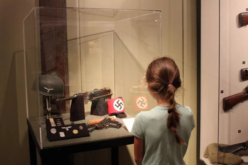 A girl looking at Nazi gear.