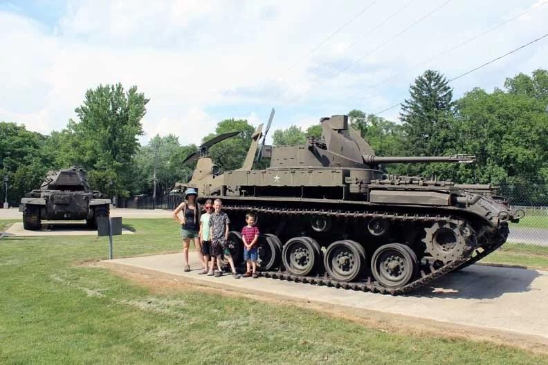 A family next to a tank.