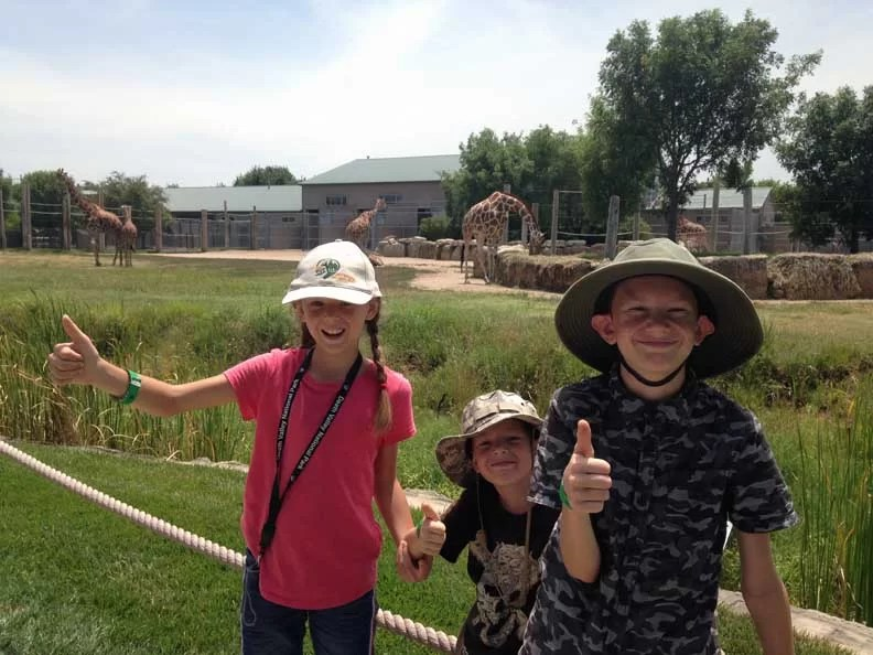 kids giving thumbs up in front of giraffes