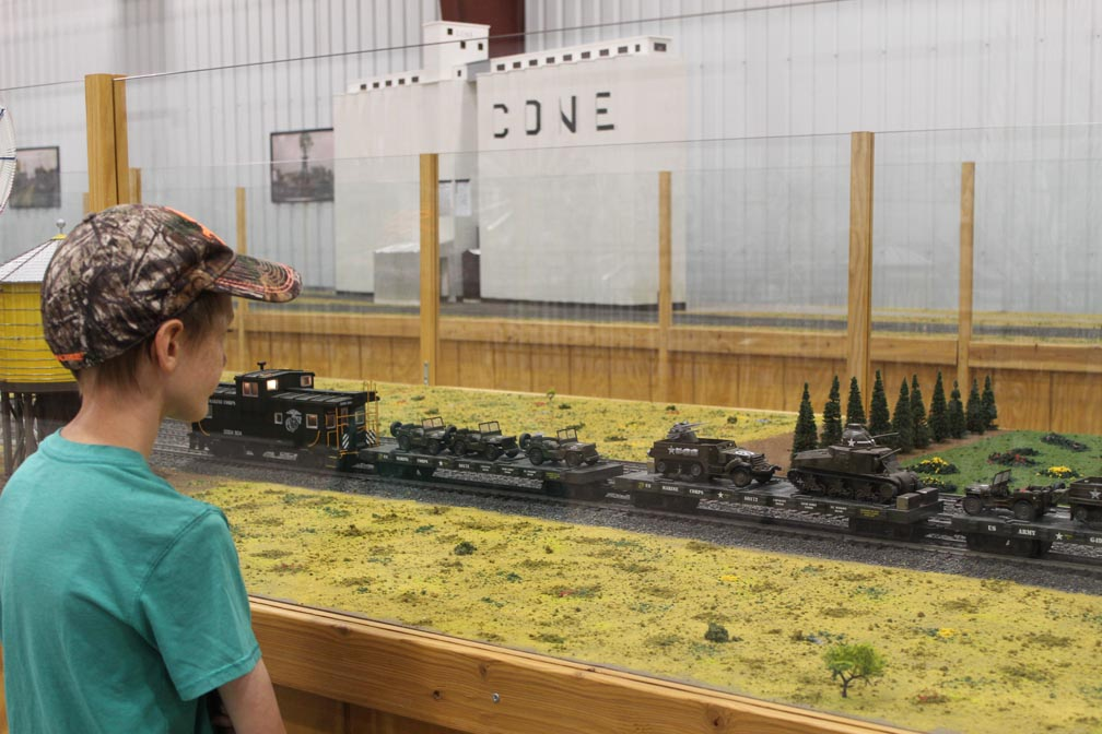 boy looking at model military train
