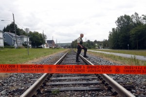 A Quebec Provincial Policeman crosses the railway tracks inside the exclusion zone in the town of Lac Megantic, Quebec.  Hundreds of residents were evacuated from their homes when a runaway train loaded with crude oil exploded on July 6.