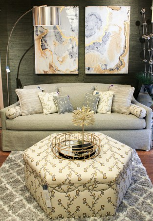 Couch with varying pillows and fabric covered ottomon and circular tray and metallic decor piece feel warm with the modern two piece painting on the wall. Electric pieces that work for at home feel.