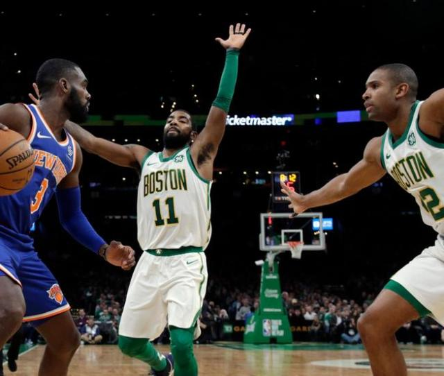 New York Knicks Guard Tim Hardaway Jr  Looks For Room To Move Against The Defense Of Boston Celtics Guard Kyrie Irving  And Center Al Horford