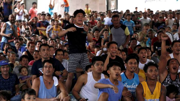 Fans of Philippine boxing champion Manny Pacquiao cheer as they watch the WBA welterweight world title boxing match between Manny Pacquiao and US boxer Adrien Broner, on a screen in a basketball court in Manila, Philippines. (Image: Reuters)