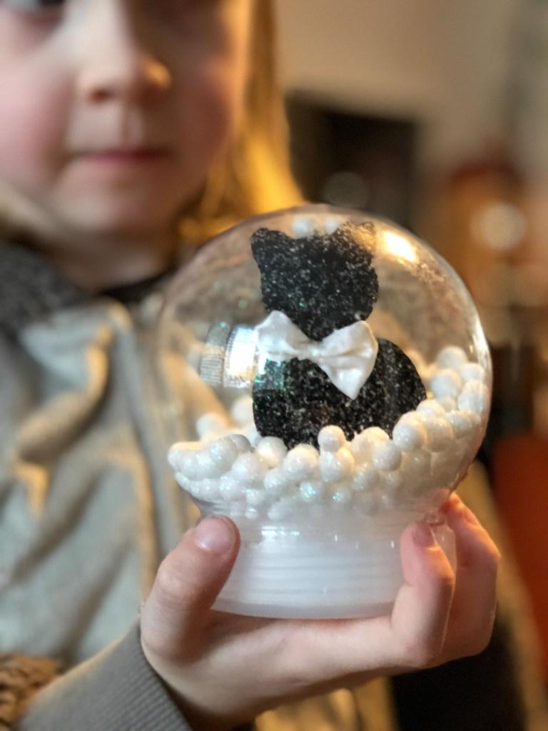 kid holding a snow globe