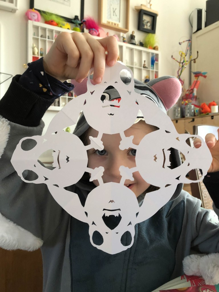 child cutting paper snowflakes