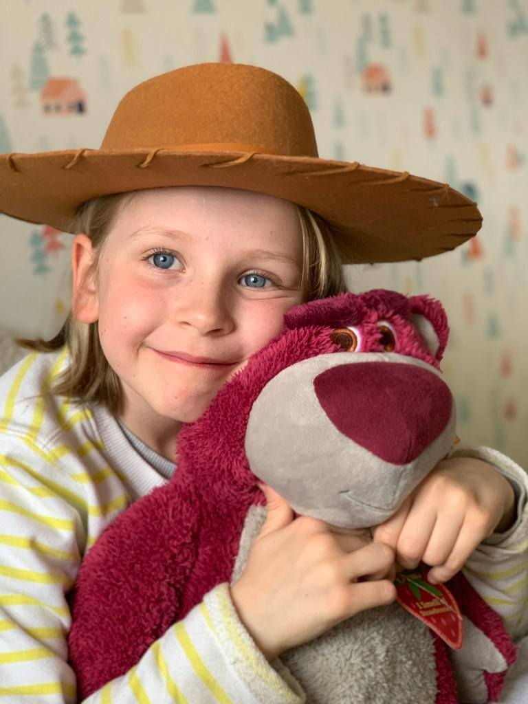 girl cuddling Lotso from Toy Story 4