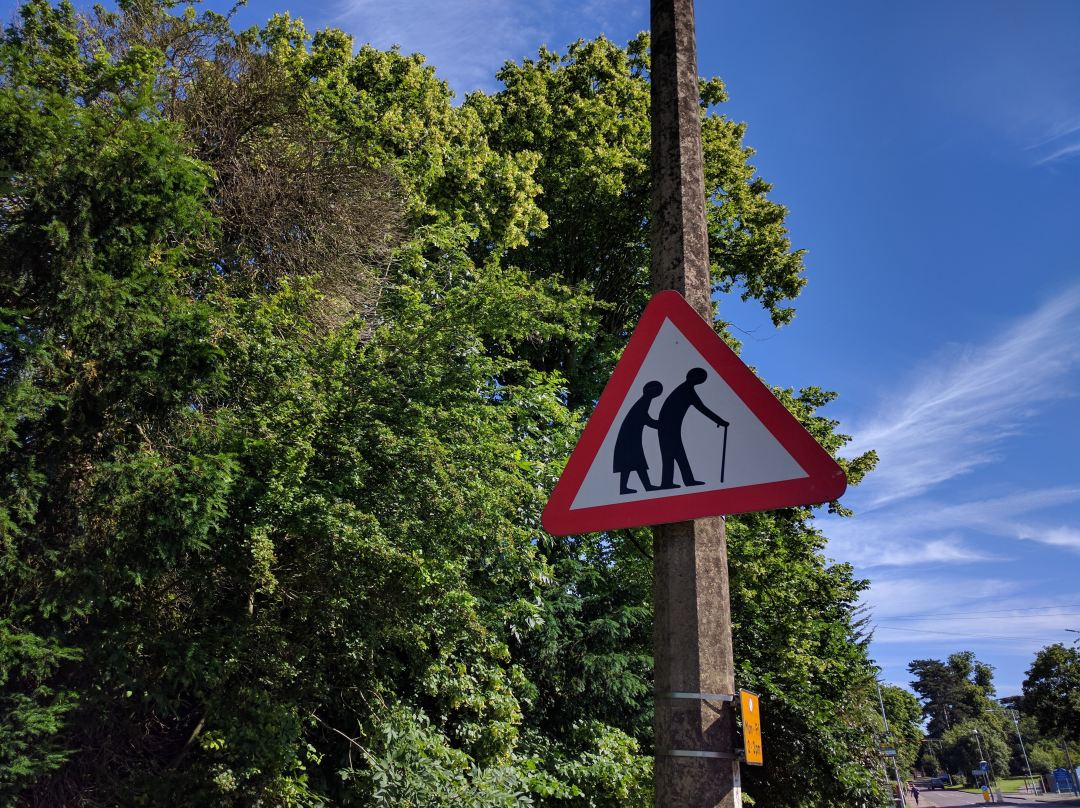 photo of a road sign featuring elderly people crossing