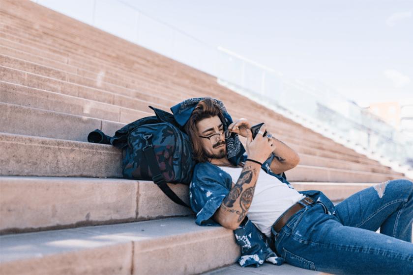 man op de trappen liggen en staren naar zijn telefoon
