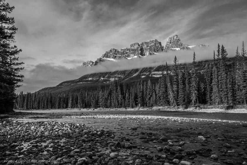 zwart en wit landschap van een rivier die naast een bos onder wolk overgaat behandelde sneeuwbergen